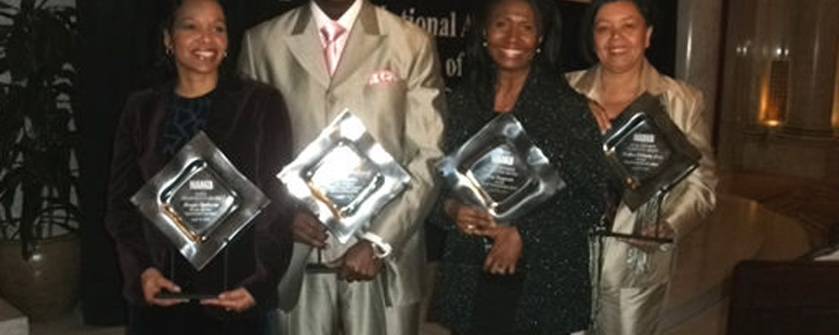 four people holding awards