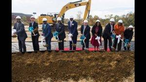 business people in hard hats breaking ground